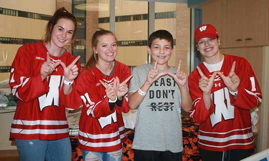 "Women from the hockey team — Lauren Williams, Baylee Wellhausen and Sydney McKibbon — throw up the ""W"" with one of their biggest fans"