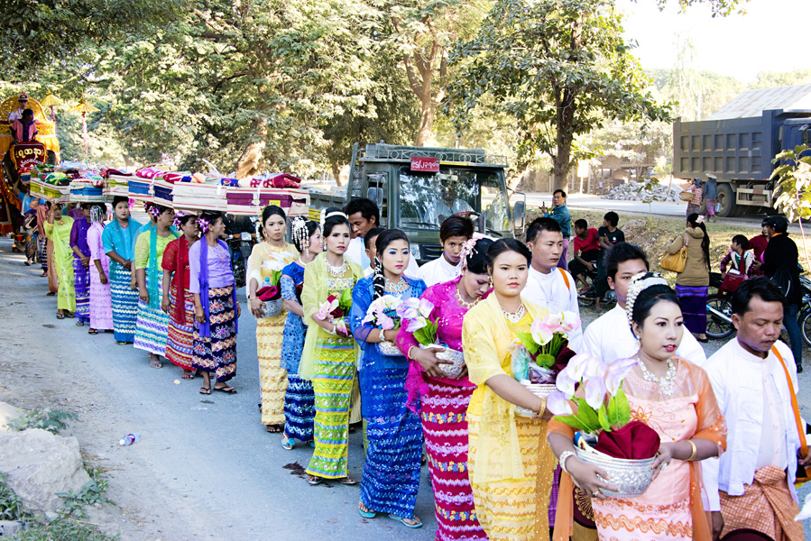 Burmese women dressed in traditional clothing carrying offerings in a Burmese Shinbyu procession in Myanmar