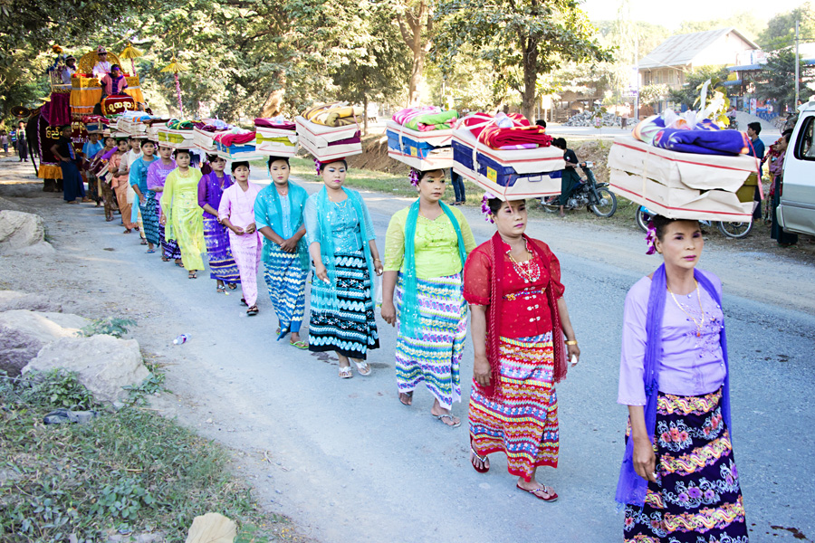 Burmese women carrying personal items in a Buddhist Shinbyu Procession in Myanmar