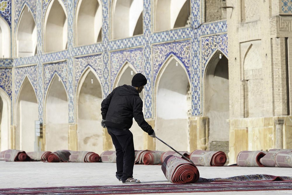 Man Unrolling Prayer Rugs