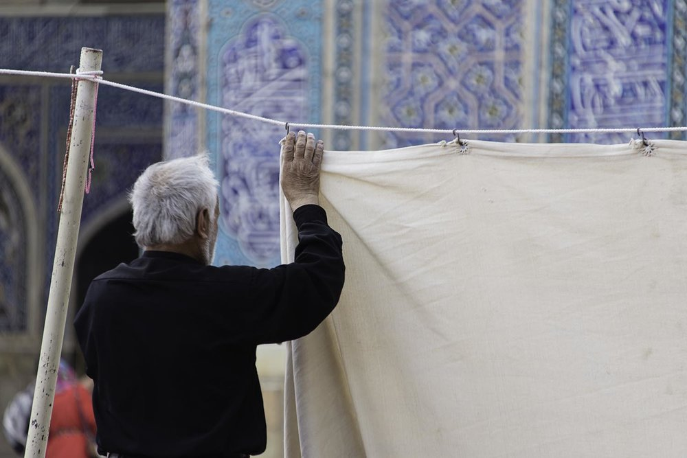 Man Hanging Prayer Curtains Outside Mosque