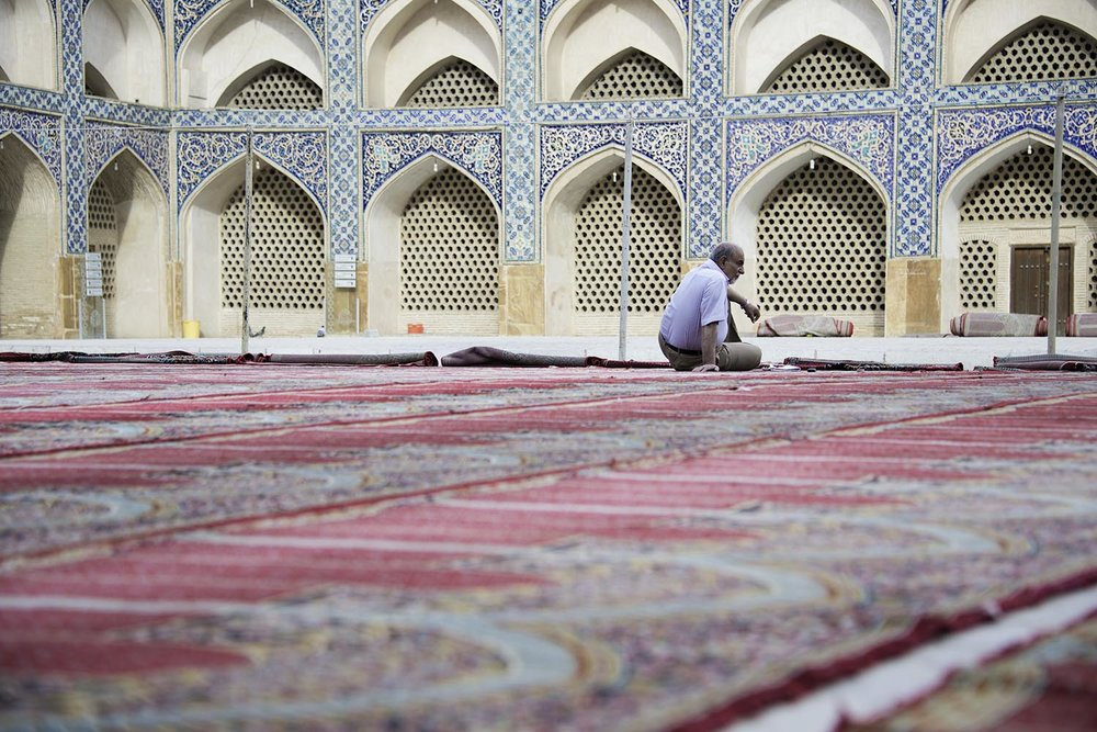 Man Sitting on Prayer Rugs