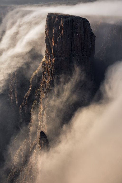 This was one of my finest mornings of landscape photography I have ever experienced. A bland sunrise turned into an epic display of wind and mist coming from Lesotho and falling over the escarpment edge for more than an hour. The falling mist engulfed the landscape emphasizing the dynamic cliffs and pinnacles of a treacherous and beautiful Drakensberg Amphitheatre landscape.
