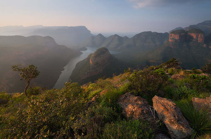 The sun sets lower to the horizon casting golden light onto the Blyde River Canyon landscape. The hazy afternoon portrays an essence of glowy light, quite characteristic of this part of the country.