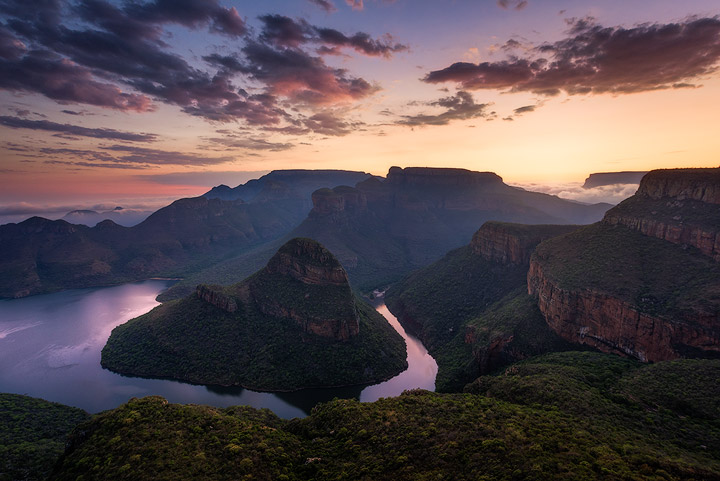 An early rising summer sun casts vibrant colours onto high clouds above the escarpment looking towards the lowveld and engulfing the Blyde River Canyon in a wonderful twilight dawn glow.