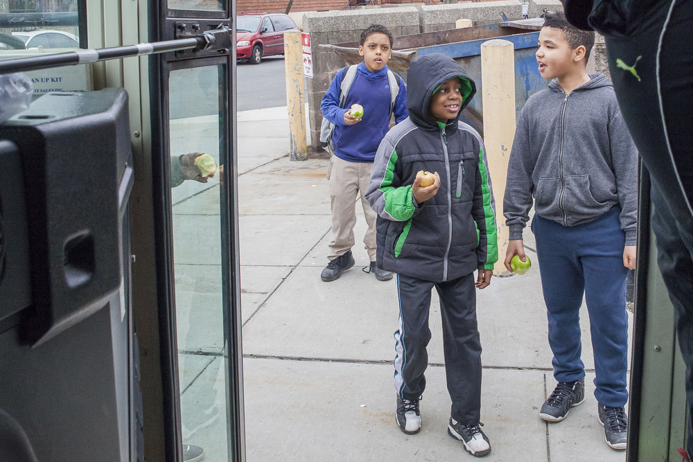 A group of boys enjoy apples they bought with the money of a good samaritan at a Fresh Truck stop near Franklin Field in Dorchester.