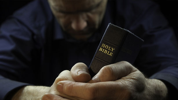 Man-praying-with-Bible-via-Shutterstock
