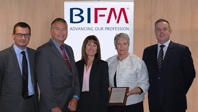 Mark Cooke, Chief Operating Officer (far right) and Martin Campbell, Deputy Director (far left), being presented with the Recognised Centre plaque at the BIFM head offices