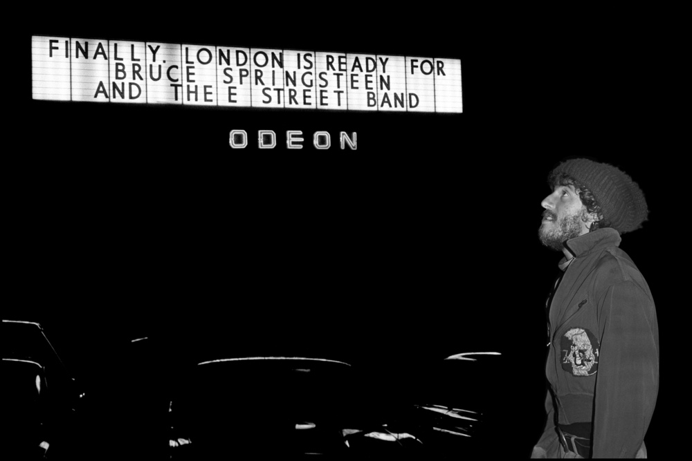 Bruce Springsteen - Hammersmith Odeon - London 1975  In 1975 Bruce Springsteen was hailed as the savior of Rock and Roll by the CBS Hype machine in America and he came to London in November 1975 to play two shows at the Hammersmith Odeon. But, Bruce was a shy and sensitive artist and the hype bore heavily on his shoulders. There was a party after the show in the Balcony Bar and I knew that the only way for him to get there from Backstage was to walk around the side of the building. I waited near the front of the Theatre with some fans when he walked alone towards us, wearing the same wooly hat that he had performed in, he looked more like a homeless person than a Rock Star, he signed a couple of Autographs and then looked up at the big sign above the entrance. 'Finally London is Ready for Bruce Springsteen' it proclaimed. I took this photo exactly at the moment he was reading it. His mood changed immediately and he appeared agitated and upset, I took no further photos but watched as he ripped down a poster inside the Theatre before going upstairs and joining his party, after talking to a couple of the Record Company Executives he told his manager to instruct CBS to stop the hype and let the music sell itself. This is a very intimate moment in Rock history and I'm very lucky to have been in the right place and the right time to witness it.