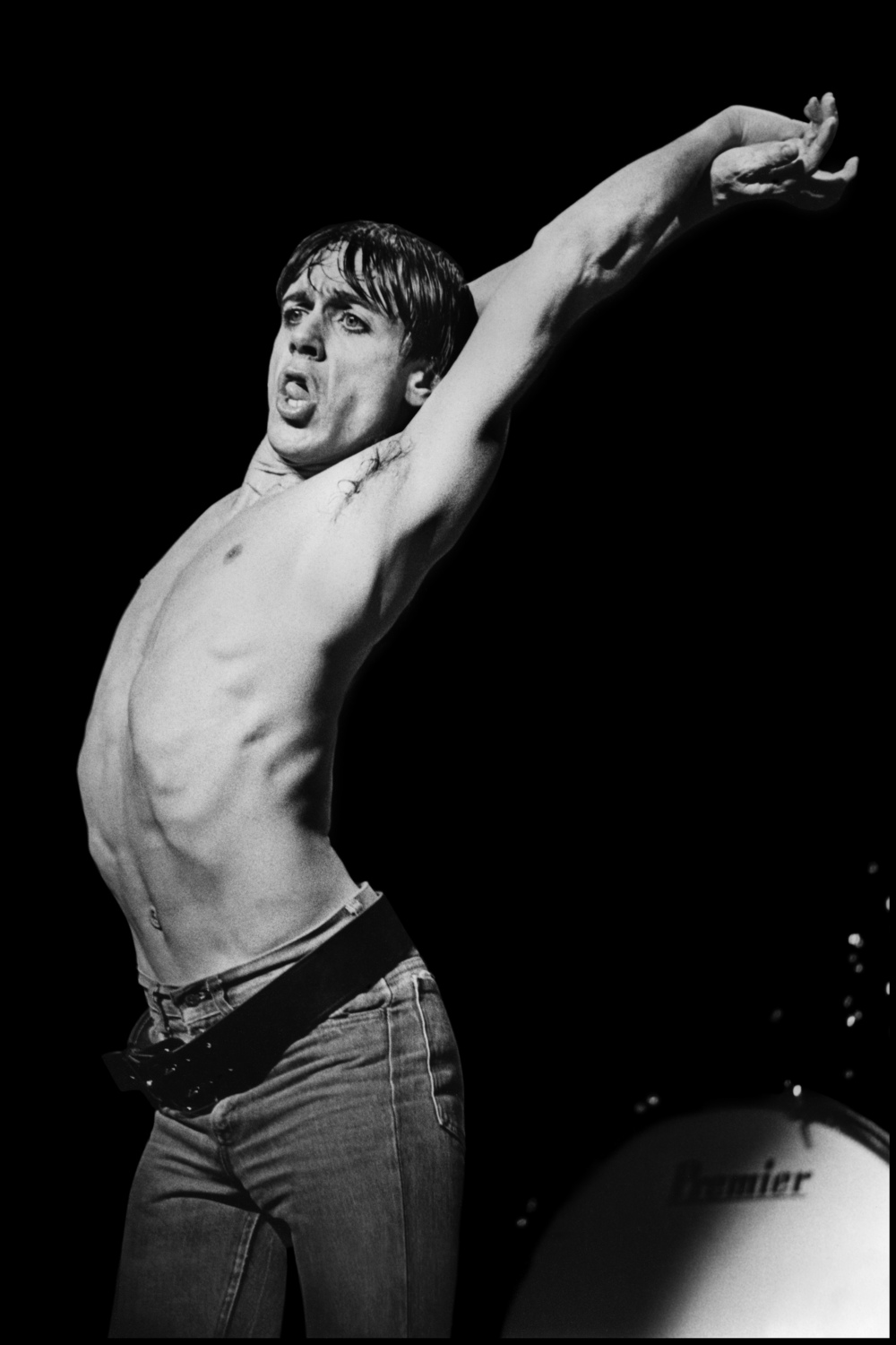 Iggy Pop - Manchester 1977  When Iggy Pop released The Idiot in 1977 he did a British Tour featuring the album's producer, David Bowie, on keyboards. This meant that security was very tight, and photographers were not invited.  This did not stop me going to the first show at Friars in Aylesbury. In an attempt to avoid the security personnel I ended up in the roof looking straight down at Bowie, but the lights were terrible and I knew I needed to try again.  So Tony Parsons and I went to Manchester a couple of days later. This time security was even tighter and I was unable to get my cameras into the show. But the next night, in Birmingham, I strapped the lenses to my ankles and hid the cameras under my clothing, having seen the show twice I knew exactly when Iggy would throw a few shapes and decided to limit myself to those numbers.  This time I did much better, I got quite a few good photos, including this one which pretty much sums up Iggy, having got what I needed I kept my cameras hidden for the rest of the show, I was not going to take a chance that I would get caught, and luckily I didn't.
