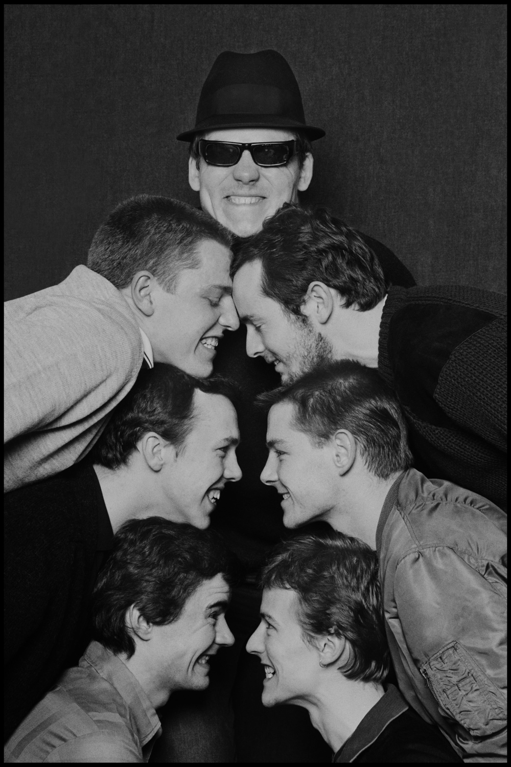 Madness - Glasgow 1980  Because I worked for the Specials I knew the chaps in Madness from the Two Tone Tour, but I took few photos as they had their own favourite photographers and I did not want to intrude.  Then they quit the Tour and were replaced by Dexy's Midnight Runners, another great band from that era, with a leader who had more passion than anyone I had ever met.  When Madness subsequently went out in their own tour I was commissioned to photograph them. To be honest anyone could have done these guys, posing came naturally and they had a cohesion that made for great photos every time. But instead of the action packed photos they were used to doing I decided to simply take a photo of their heads, this picture was done in a couple of minutes backstage in Glasgow.  Not long after this I ended up on a train to Oxford with them, I was just going to their show and had no cameras with me. I got talking to Suggs and Kennedy's assassination came up, he had little recollection of an event that causes everyone from my generation to remember exactly where they were when they heard the news.   Then it dawned on me, Suggs was the first person I knew who was born in the 60's, not the 40's or the 50's. I realized that he was part of the next generation, and at the age of 27 I felt old for the very first time.
