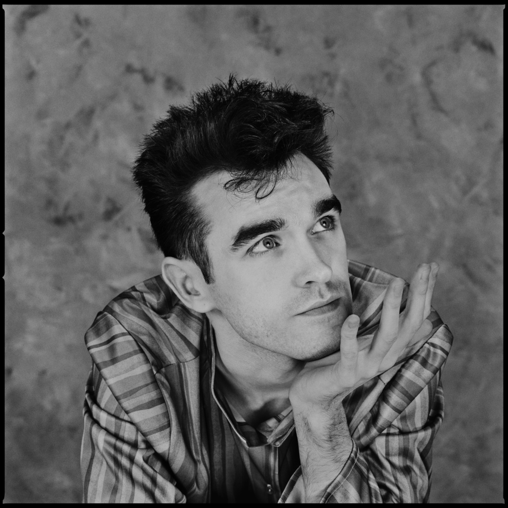 Morrissey - London 1982  I used to work a lot for Rolling Stone in the 80's, I was the photographer they came to when they needed something done in Europe. Most of the time it was American bands I had never heard of, but sometimes it was British ones.  So one Sunday afternoon in 1982 the Smiths showed up at the door of our little studio in a Bayswater Mews, to say they were young and inexperienced at photo shoots would be an understatement. They took direction well, but they had yet to really get their individual looks together and their clothes were pretty bad.  Doing what we often did we gave then black turtle neck sweaters and decent jackets to wear, but the singer, clad in this terrible rayon smock refused to wear anything else. He seemed to only have one name too, that of Morrissey.  Having done some reasonably decent group shots we turned our attention to the singer. He really had no clue as to what to do now he was on his own, it was kind of sad really, he was the front man yet he hardly had as much presence as a tin of cat food.  For 30 years these photos of him remained unseen, but, on closer examination there were one or two frames where he looked pretty good. I would never have guessed that he would go on to become so successful, but you never can tell, success is a fickle thing.