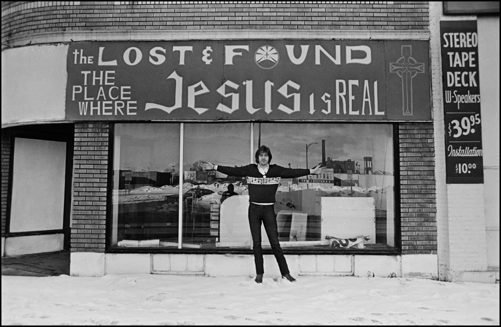 Nick Lowe - Buffalo 1978For any British band touring America in the 70's the first thing you did after checking in to the Hotel/Motel was to hit up the Thrift Shops and Pawn Stores.  Back then there were still gems to be had at both, and musicians rigorously checked them looking for guitars and other instruments, on this particular day Charles Shaar Murray found a Telecaster in great condition, in fact he lent it to Nick so that he could play Heart of the City in the encore at Elvis's show that night at the University.  Thrift Shops, also known as Sally Ann's (Salvation Army) were great places to find cool stage clothing, and also winter coats, much needed as this trip occurred during the great Blizzard of '78.  These were the days before Johnson and Johnson started being the place for Rock Star Threads, us chaps could not get enough cowboy shirts, leather jackets, cashmere coats and a whole lot more.  The Thrift shop in this photo is in Buffalo, and the temperature was 15 below, but Nick Lowe is a hardy chap and never even bothered to wear a jacket over his legendary musical note sweater.