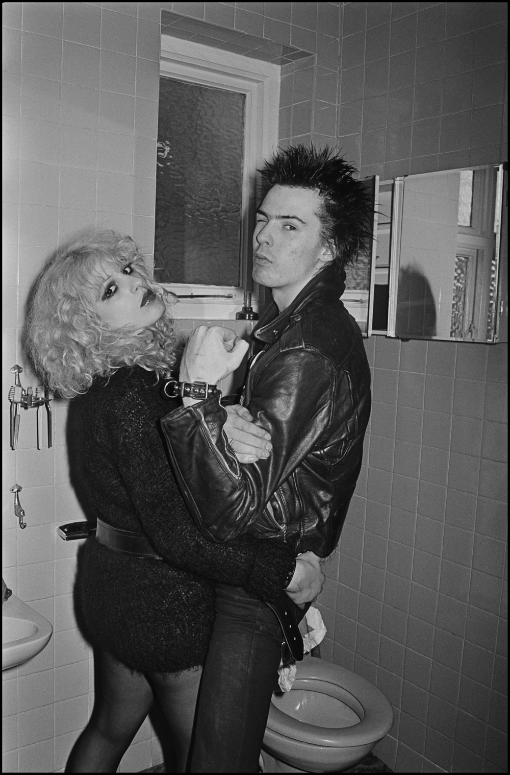 Sid and Nancy - Cricklewood 1978 When I shared a house with Phil Lynott from Thin Lizzy there were often musicians around, that veritable duo Cook and Jones from the Sex Pistols were frequent visitors. Sid and Nancy came over with them a couple of times, they did not behave like they did in public, they were well behaved and polite, they loved watching black and white Elvis Presley movies on Philip's video recorder, which was a rarity back then. Some nights we would go to bed whilst they were still watching the TV, I would go downstairs in the morning and they would be gone but the living room would be clean and tidy, they had even emptied the ashtrays, not exactly what you would expect them to do. They were always respectful to Philip although Sid was not really interested in getting tips from him on bass playing, one night I asked them to pose for pictures in our bathroom, they duly obliged and the photo appeared on the front page of the NME. To me they were a couple that were very much in love, and Nancy did everything she could for Sid, he was quite funny really and they never caused us any trouble, their end was tragic beyond words, but it fitted the legend that they had already carved out for themselves.