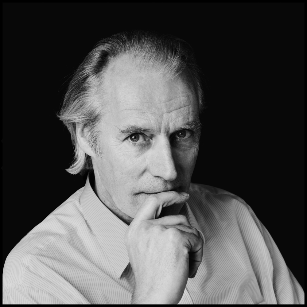 George Martin - Air Studios 1985  There are certain people in the Music Business who are genuine legends, those who help build the records we all love, people who know how to extract the very best performances out of the artists, they labour for months to make the very finest recordings, these people are the Record Producers.  When George Martin phoned up I was truly honored, this was a man I had heard many stories about, my friend Chris Thomas had been his Engineer on the White Album, without George the Beatles may never have reached the heights that they did, he wanted his portrait taken, the prospect filled me with excitement and enthusiasm, especially as he is also an extremely handsome man.  We arranged to take the photo at Air Studios where he said he would be working, it was a place we had been to many times, we often set mini studios up in the bathroom, or the relaxation area, or if available in the recording studios themselves. We showed up a little early so we could set up the mobile studio but he saw us thru the glass, he came out of the Control Room and told us that he was busy for the next 45 minutes, but, would we like to join him. There were two EMI Security Guards by the door and on the Mixing Desk was a two inch Master Tape, written in pencil on the box were these simple words.  The Beatles - Sgt Pepper  It turned out that he had to approve the first CD release of Sgt Pepper as it was twenty years since its release on LP and he wanted to listen to the master all the way thru just to be sure that it sounded OK, he played the tape, we sat mesmerized behind him. When it was over he rewound the tape a little to hear Day in the Life a second time. This time he pulled off everything except John's vocals, it was an eerie but incredible thing to hear, and brought a tear to our eyes listening to it. Once it was over we listened to all the backwards music at the end of the second side, in Studio Sound and with George sitting there it was like magic, one of th