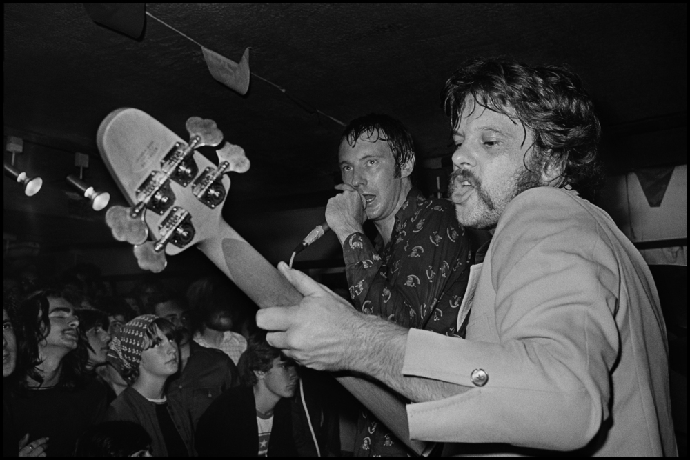 Dr Feelgood at the Hope and Anchor Benefit 1977  There was an unwritten rule about photographing live gigs, No Flash. But, there were times when you had no choice, especially in Clubs, Elvis Costello at the El Mocambo was another one. The bands don't like it because the strobe can phase them when they are not expecting it, the punters don't like it because it destroys the ambience a bit. So I used to do it very rarely, and when I did I picked my moments carefully. I knew the Feelgoods really well so they did not mind me standing on the side of the stage, but at the Hope and Anchor the stage was tiny, and the Feelgood's were a big band by now and even in this tiny club they had a huge PA, just look at the size of the monitor wedges. I was literally a couple of feet from Sparko when I took this photo, I only ever took a few frames, and once I knew I had something great I stopped. I think this shot really sums up the energy of their live act, Wilco is on the other side of the stage so I was unable to see him, but it's nice to have a big close up of Sparko and Lee in action. They were one of the best live bands ever, and this night was the best show I ever saw them play.
