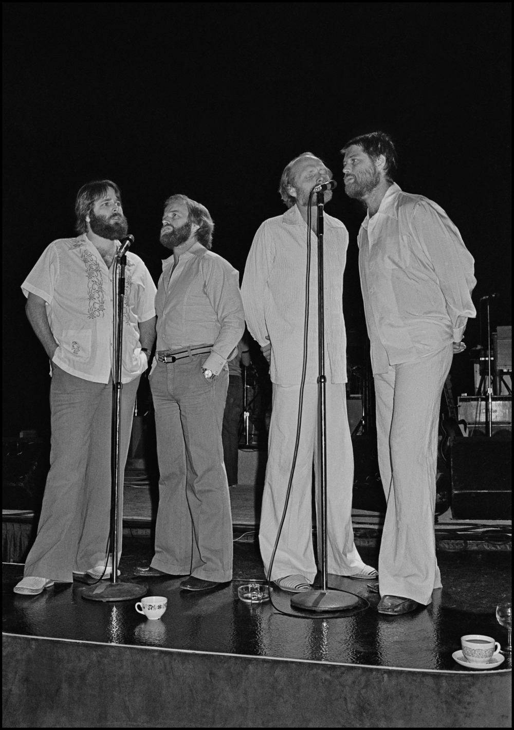 The Beach Boys - Dorchester Hotel 1977  You could describe my life as pure luck, not in getting the picture each time, that part was relatively easy, but just in terms of who I got to see and the circumstances under which saw them. This photo definitely comes into that category.   Back in the 70's the Record Companies were flush with cash and were happy spending it on themselves. CBS took this to the extreme with their Annual Conventions, these multi day events consisted of flying hundreds of Record Co Execs to some exotic location and then have their best Artists perform for them, Bruce Springsteen played the 1975 one in New Orleans. In 1977 they had it in London, on the morning of the first day Elvis Costello started busking on the street outside the Grosvenor Park Hotel, his hope was to get the attention of the CBS people, instead he became a person of interest to the Police and got arrested. Luckily he got out of jail in time to play Dingwalls later that night.  The highlight of the Convention was a performance by the Beach Boys on the final night. I was pretty good at sneaking into places unnoticed and so, along with my friend Kevin, we slipped into the Ballroom via the service entrance in mid afternoon. I did not know if we would see anything but it was worth a try. We were hiding behind piles of stacked chairs when the place started to get quite active. Then, in front of out star struck eyes, out came the Beach Boys to do a Soundcheck. Better yet, Brian Wilson was with them, he had not bern seen in public or performed with them since his breakdown and in NME land this was scoop central.   I stayed hidden for the first three numbers, behind Brian was his Doctor/Psychiatrist who would massage his shoulders between numbers, he also shouted out the words to the songs acting as a sort of full time prompter to the shell shocked looking Brian. Figuring that they might only do four songs I took my chance and darted out from my hiding place, I scurried to the front of the stage and took five very quick frames before running out of the Ballroom, thru the Hotel Lobby and out on to Park Lane.   I had my photo and nobody was going to take it away from me. After developing it I noticed the two teacups on the floor in front of their feet. To me it really adds to the impact of the image by adding just a hint of the surreal to it. As I said I was really fucking lucky, I really did have the best job in the world...