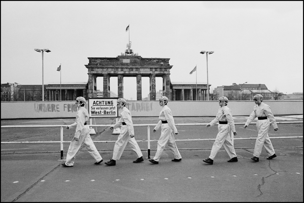 Dev at the Brandenburg Gate 1978  I went over to Berlin to photograph Devo, we did all the normal photo shoot stuff in the afternoon before they had to go to the Soundcheck.  But it still said nothing other than, here are a bunch of weird Americans from Akron, Ohio wearing yellow paper suits and funny hats. I did have a better idea, but it would take a lot of persuasion to achieve it.  They had to leave for the airport at seven am, I suggested leaving an hour early and going to the Brandenburg Gate to do photos. Berlin was still a divided city and the Wall separated east from west. I ran it by Gerry, I ran it by Mark, once I had their votes the rest of the band agreed, and so off we went.  When we reached the Wall it was completely deserted, the band changed into their outfits on the coach while I checked out the best position for photographs. Then the band quickly posed together for a few frames, but it still didn't say that much about the situation. I asked them to march back and forth in front of the gate a few times.   It was to be my East German homage to Abbey Road.  Out of the corner of my eye I spotted some Russians on top of the gate, with what I assumed were binoculars. Just as the band crossed for the third time the Russians stood up and I saw it was not binoculars they were carrying it was machine guns. Then a bunch of German came out of the loudspeakers, it scared the life out of us, in fact the frames are not level because I was seriously spooked by the situation.  They scarpered quickly back to the bus, I joined them and in moments we were soon on our way out of the country, the adrenaline rush was pretty strong, but, I doubt if the whole thing lasted more than three minutes, machine guns have that effect on people.