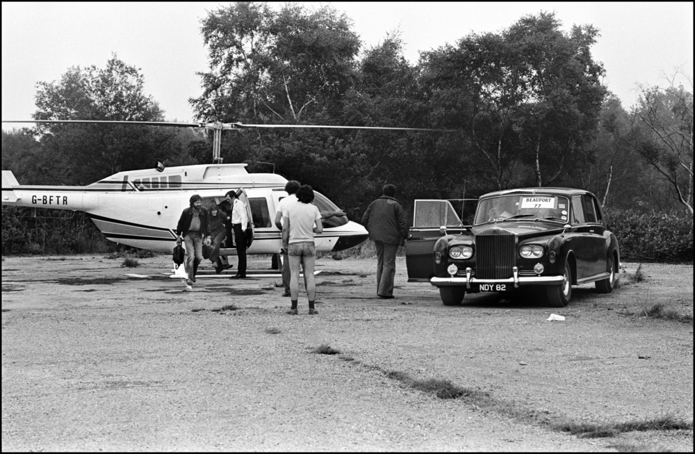 Eric Clapton Arrives at Blackbushe 1978  Here is a photograph that shows the level to which Rock Stars are pampered. It is taken Backstage at Blackbushe Airport at the Bob Dylan Concert.  Dylan was quite happy to arrive in a coach with his Band, he enjoyed looking out if the window at the surrounding British countryside, but Eric Clapton had a different idea, he wanted to excerpt the minimum effort to get to the gig, and wanted it done in the shortest time possible.  So a Helicopter was sent to his Country House where it landed in on his lawn. Eric walked the short distance from his house to the waiting Helicopter.  After a journey of less than thirty minutes he arrived at the Gig, the Helicopter landed about 200 yards from the Backstage area, but to save him from any physical exertion and to keep him in the luxurious style he was used to a Rolls Royce was parked nearby.  Eric then walked over to the waiting Rolls, got into the back seat, and was driven to his dressing room, a journey which took less than a minute to complete.  How nice it must be to live inside a superstar bubble, to have everything at your disposal, to simply have to walk about twelve steps from Helicopter to Rolls Royce.  But, to me, as well as documenting one of Rock's more surreal moments, it shows off the impeccable style of the British Roadie, just take a look at the guy's shorts, it's living proof of why Roadies often got more girls than the Band.