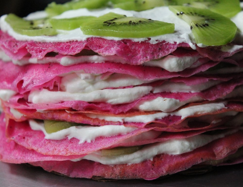 dragon fruit crepe cake layered with kiwi and whipped cream