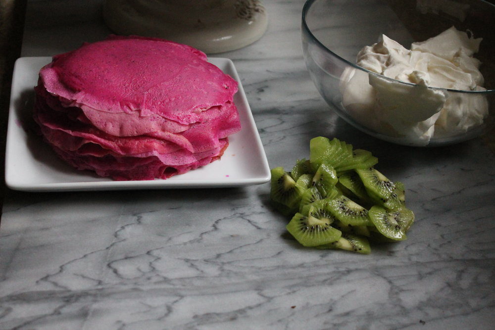 dragon fruit crepe cake prep with kiwi slices and freshly whipped cream