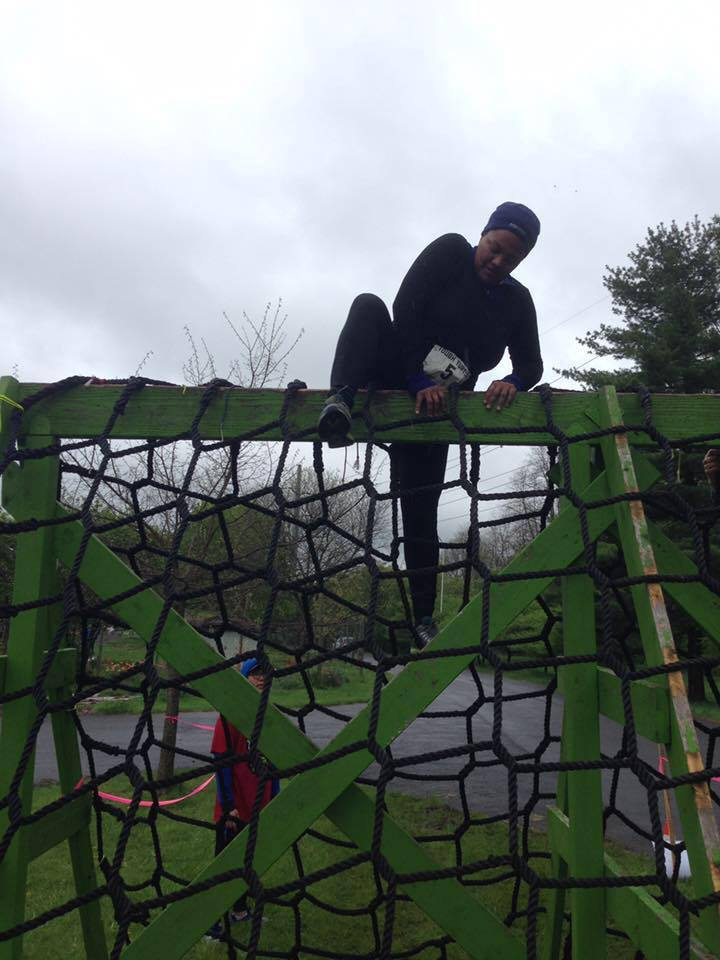 "Obstacles are just that, obstacles, until we climb over them. Here Michelle tackles the last obstacle during the popular ""Tough Turtle"" team challenge that benefits the Ithaca Children's Garden."
