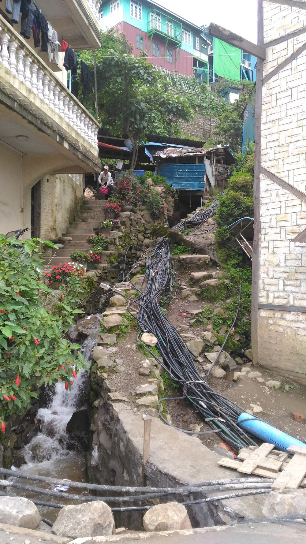 Tens of exposed and entangled pipes distribute water to individual houses