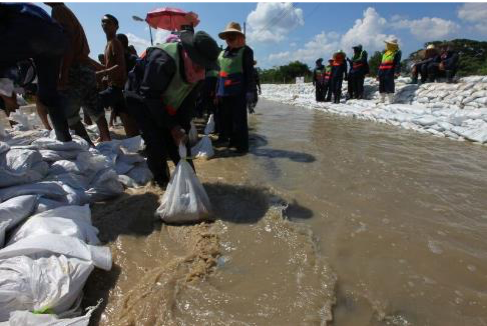 Volunteers and members of the Royal Thai Army, military police, fill and place sandbags to redirect flooding in the northern Sai Mai district in October 2011. (Credit: Cpl. Robert J. Maurer via Wikimedia Commons)