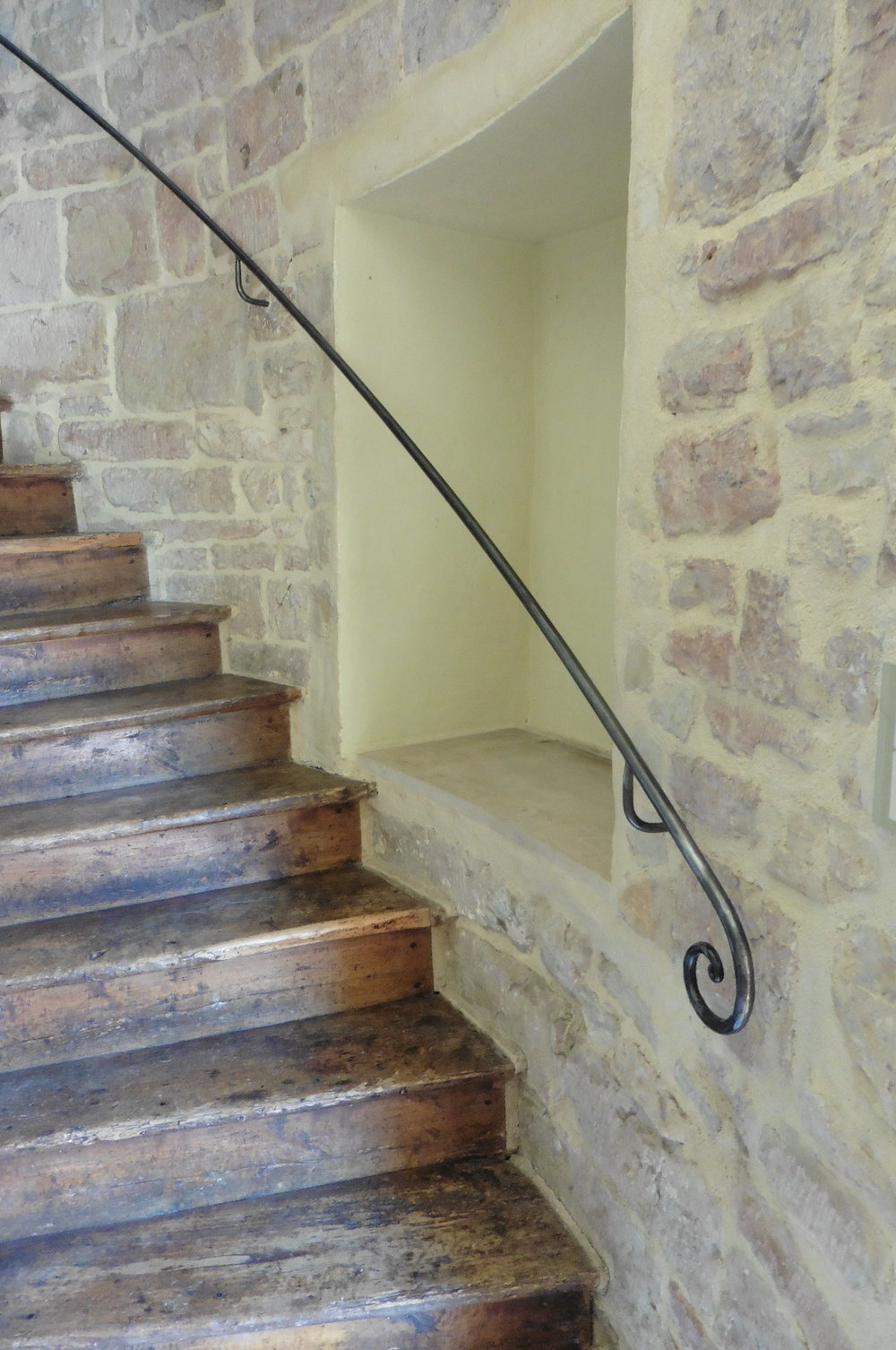 A tower, a narrow curving staircase and the need for a handrail for a safe ascent and descent. Very simple, forged end handrail, finished in clear varnish.