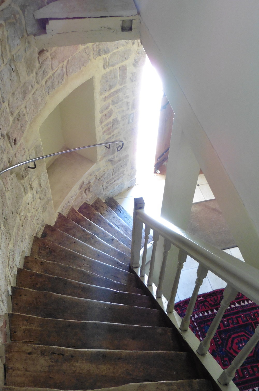 A view of the handrail from the top of the curving staircase.