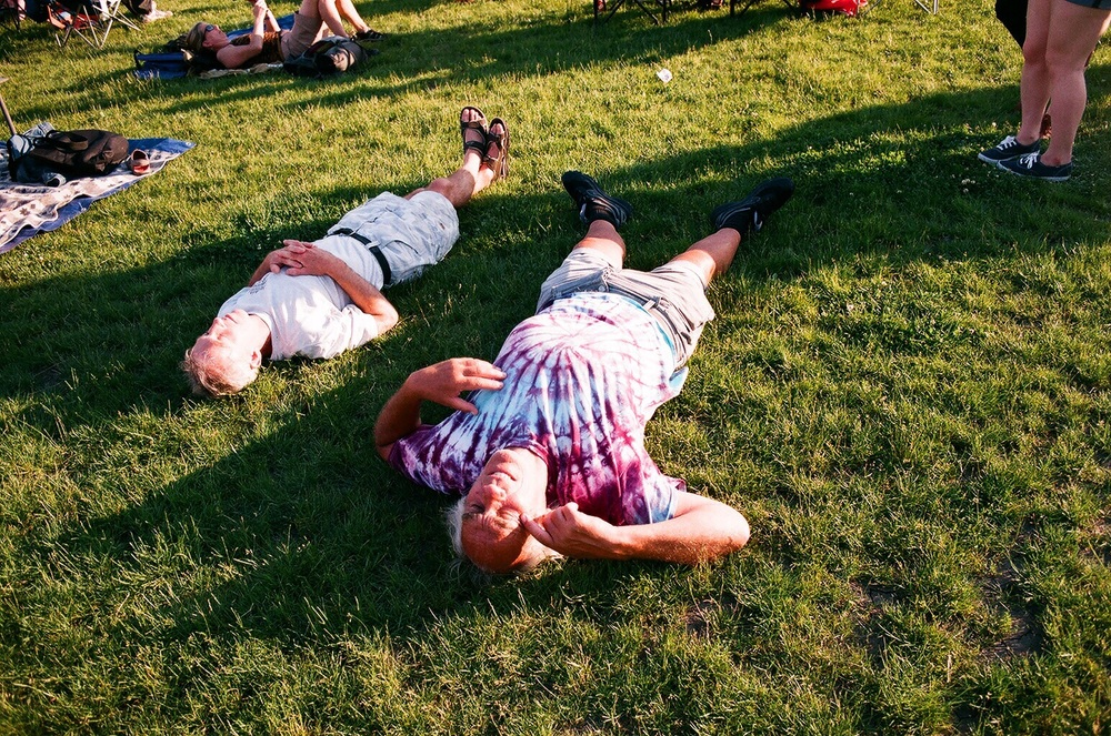 Two festival goers listen to live music laying down in the grass. Chicago Blues Festival 2016, Blake Pleasant