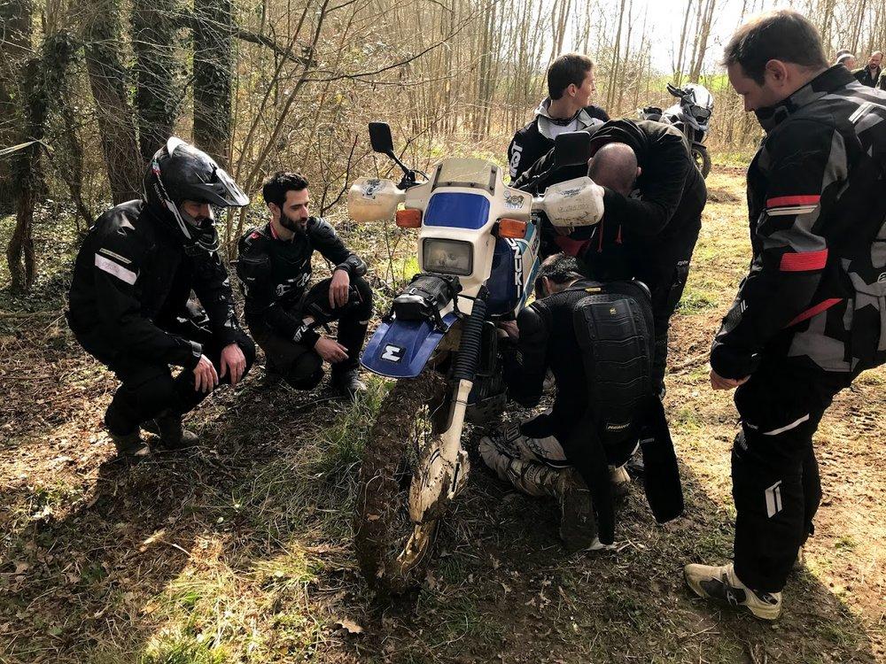L'équipe affairée à faire redémarrer la moto de Vincent, lui-même au bout du bout.