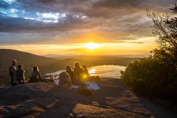 group overlooking sunset from a mountain