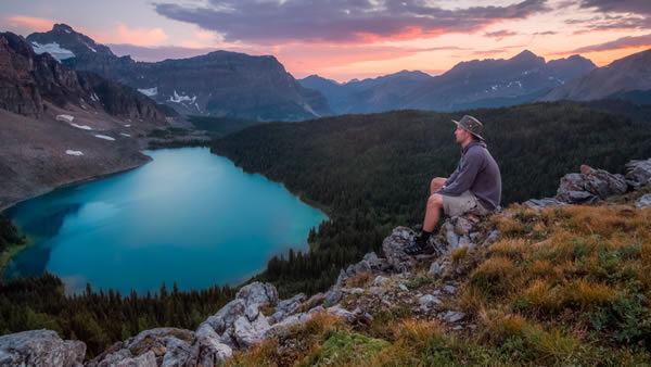 man overlooking mountain lake