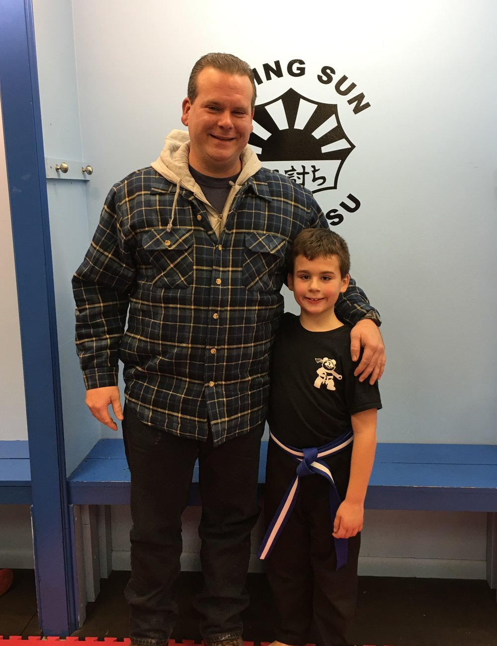 """Anthony and son AJ """"Rising Sun Jiu-jitsu has made a positive impact on my son. I have noticed several positive changes in his behavior. He is more assertive and confident both at home and at school. My son is confident in his ability to defend himself from bullying. Sensei Watts does an incredible job with his students instilling self- confidence and building character."""" - Anthony Haywood"""