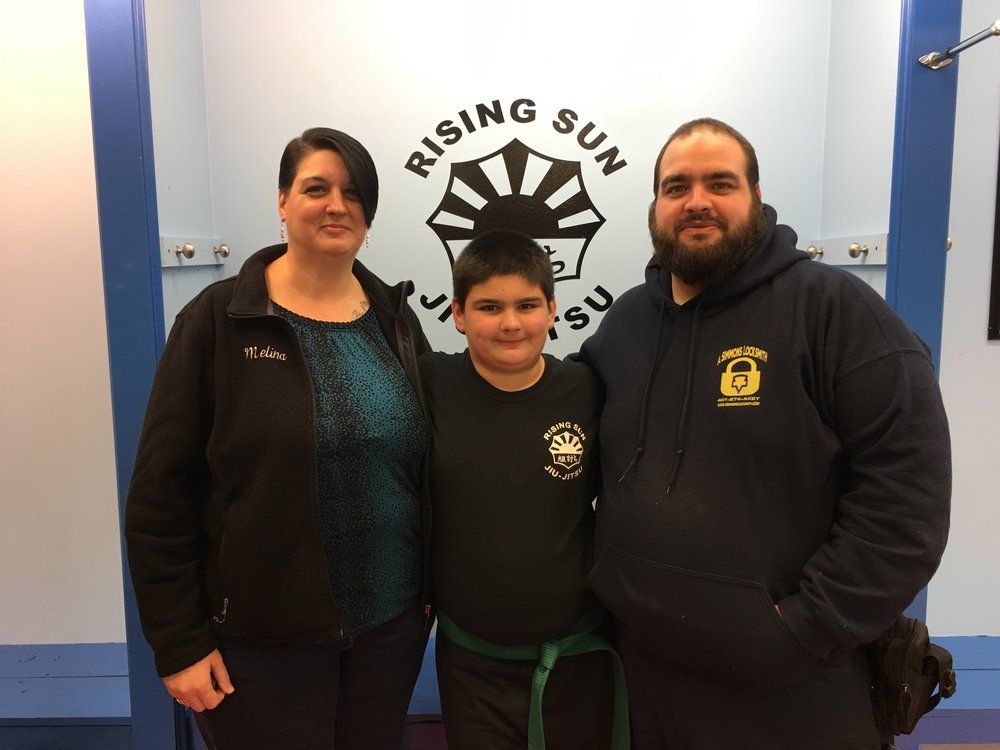 """The Simmons Family """"We first met sensei Dean of Rising Sun almost 2 years ago at an after school program at my son's school and we have loved it ever since. Rising Sun encompasses teaching the students respect, self defense, self confidence and to never give up and always do your best no matter what. I am proud to say that my son is very respectful both at home and at school, he feels confident with the tools he has been given to defend himself against bullies and strangers and he strives to be the best that he can be. We are proud to be part of the RSJJ family!"""" -Melina and Robert Simmons"""