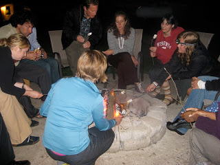 Fellows and fellowship staff spend time sharing stories and roasting marshmallows over a campfire
