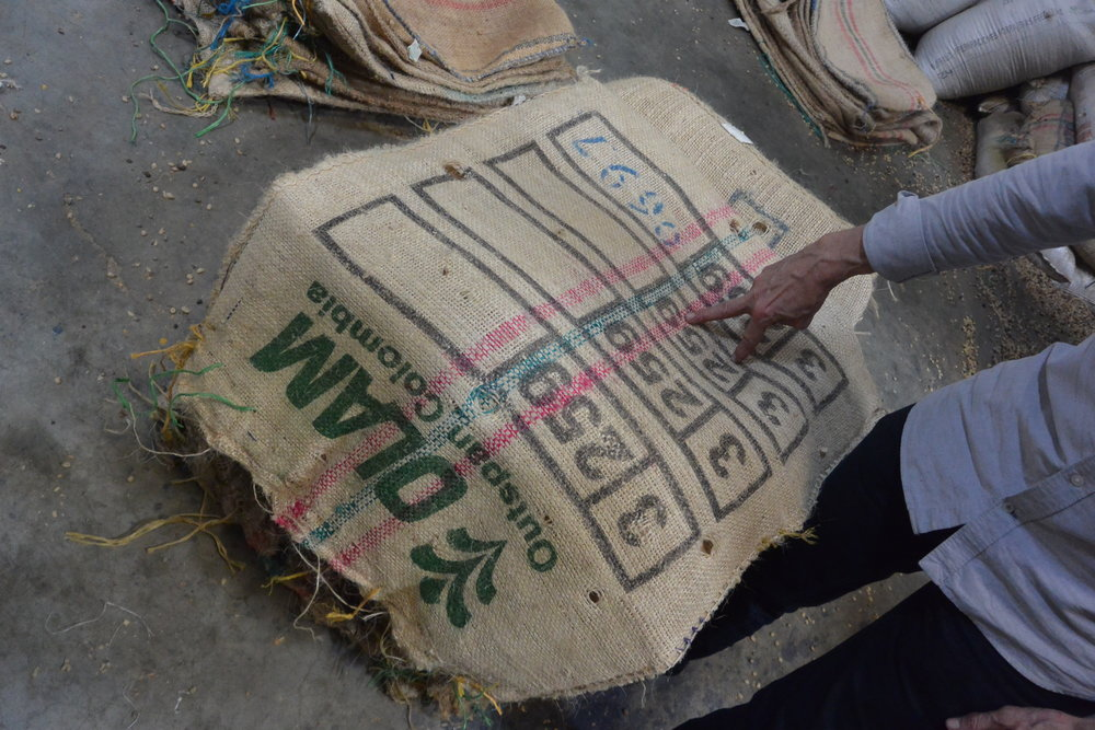 Roger demonstrating the markings of a coffee bag at a Colombian mill