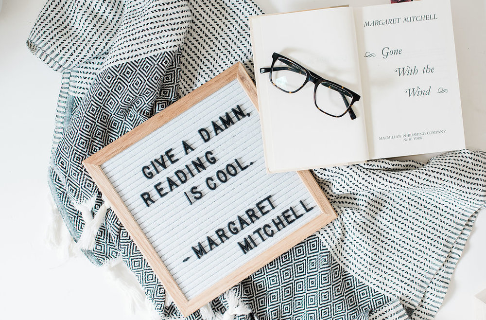 Black and white blanket, letter board with a silly quote, open book, and a pair of glasses.