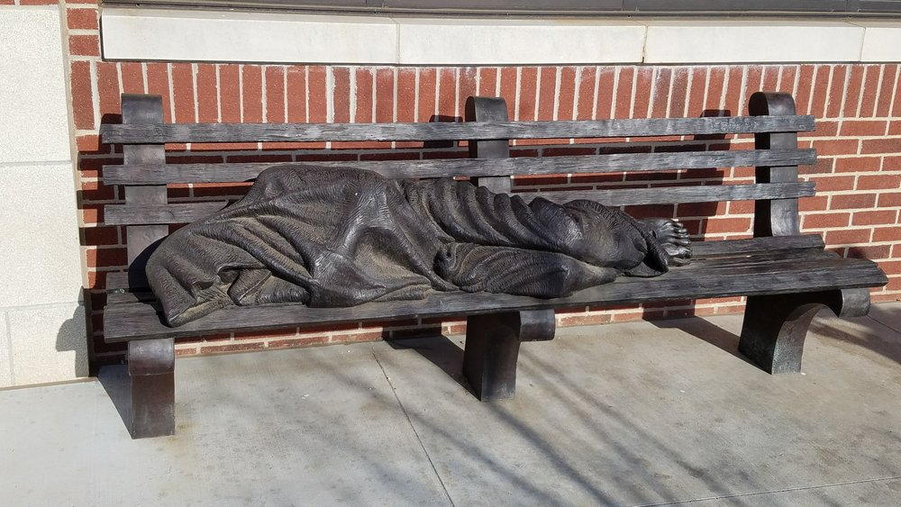 """Homeless Jesus""-by sculptor Timothy Schmalz The pope called. He wants this bench at the Vatican. The article in the comments talks more about this, but they said people stop day and night and sit. They told us that the bench stays clean but the homeless Jesus always has a layer of dirt. — with  Catholic Charities of the Archdiocese of Oklahoma City . Pretty interesting article as well: http://okgazette.com/2016/06/17/catholic-charities-new-facility-helps-the-organization-run-its-programs-more-effectively/"