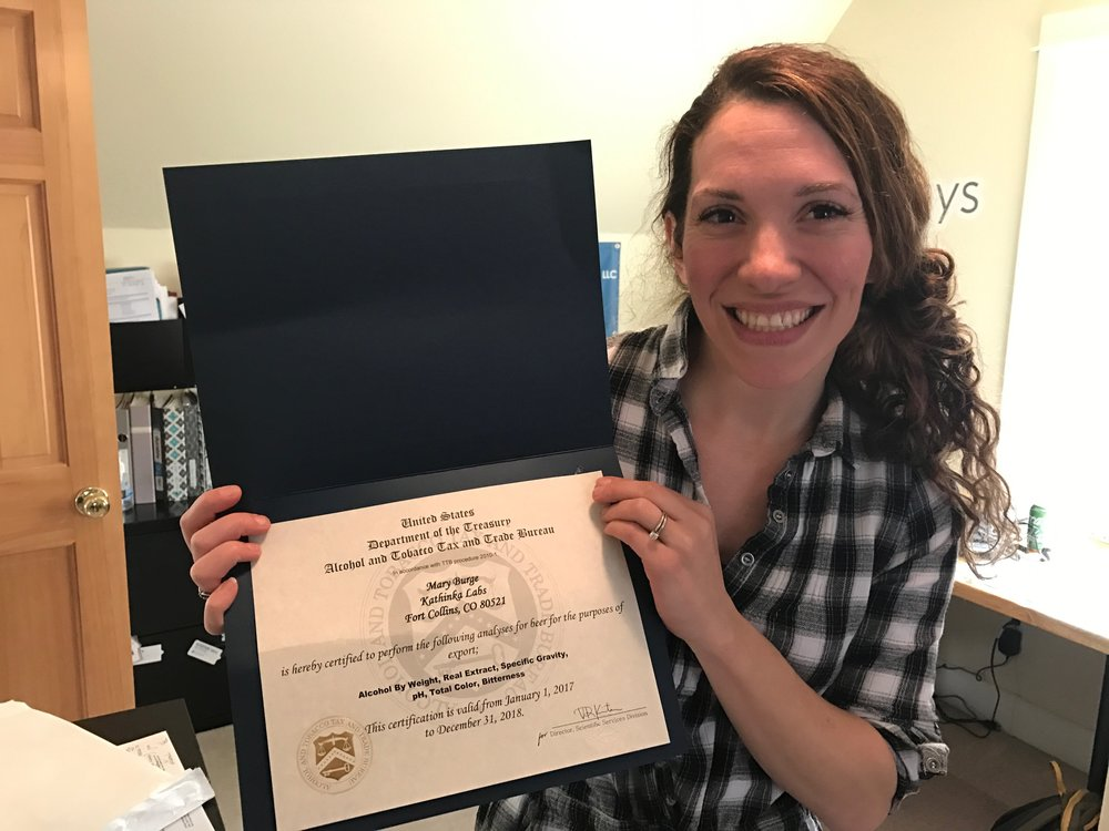 Mary Burge, Lab Director, shows off her TTB certificate.