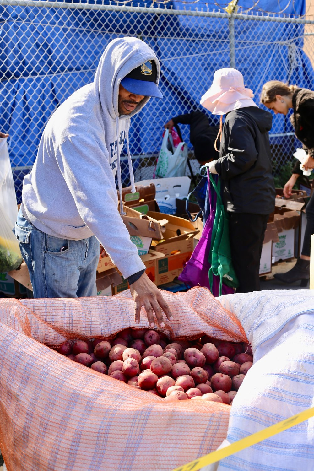 Andre inspecting potatoes at a weekly free farmers market. Photo by Colette Krey