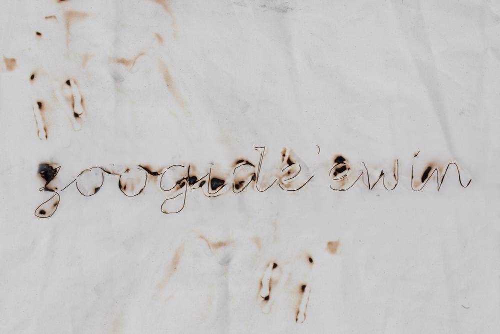 ZOONGIDE'EWIN - cursive   Cursive writing of the word Zoongide'ewin burned on canvas to depict learning English with cursive writing. The beginning of losing the language.   Element: Fire