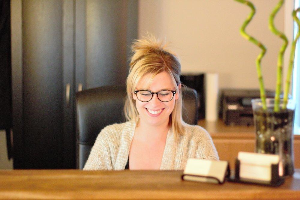 Cassie, Niasoma Bodywork massage therapist, sitting at our reception desk