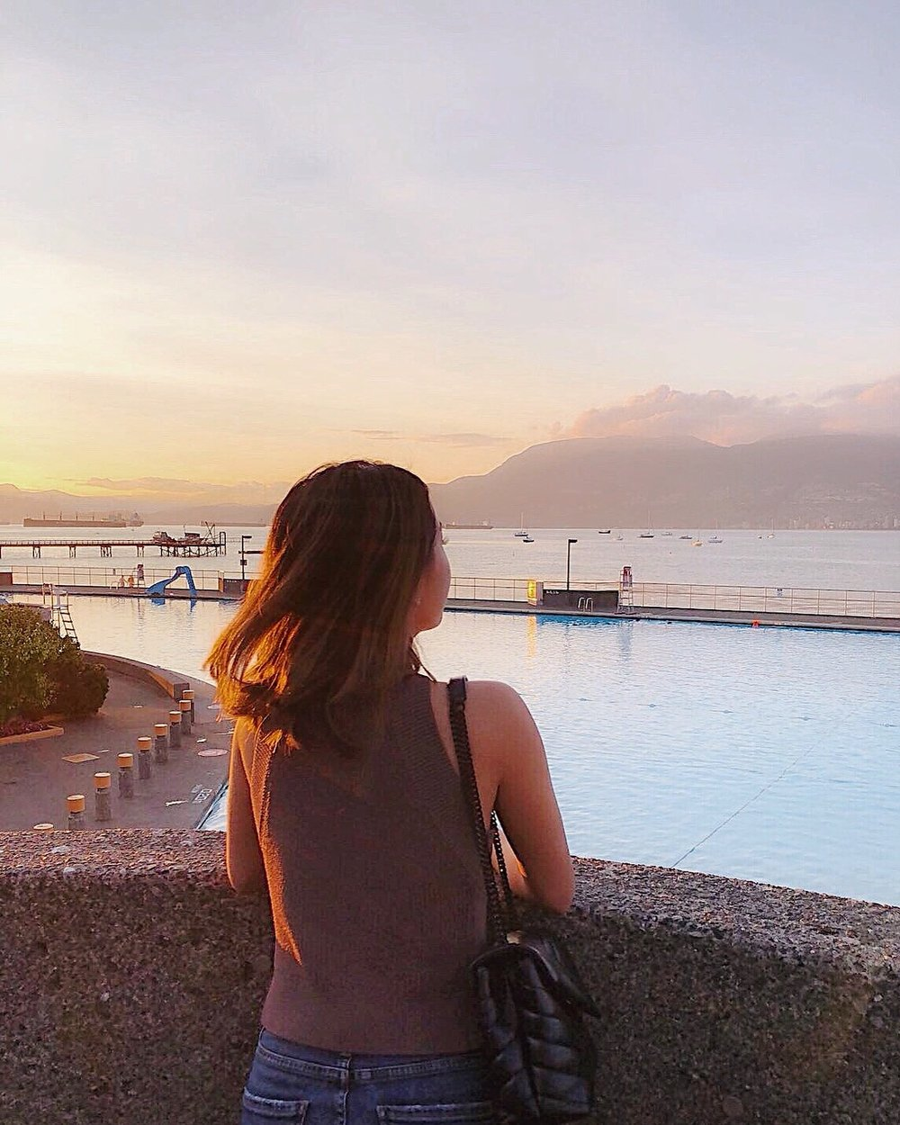 Soaking up a glorious sunset at Kitsilano Beach. Wearing Aritzia top, Agolde jeans and YSL bag.