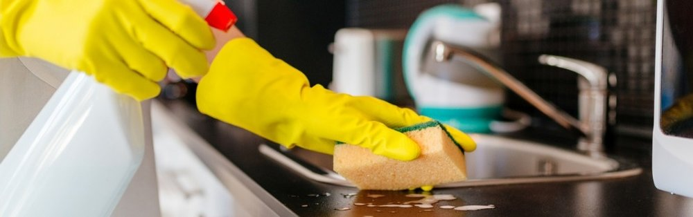 woman-cleaning-kitchen-cabinets-with-sponge-and-spray-cleaner-picture-id635801162.jpg