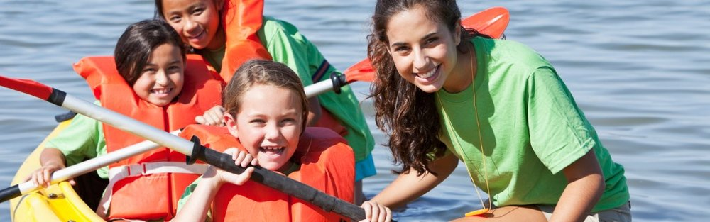 girls-in-a-double-kayak-at-summer-camp-picture-id184380779.jpg