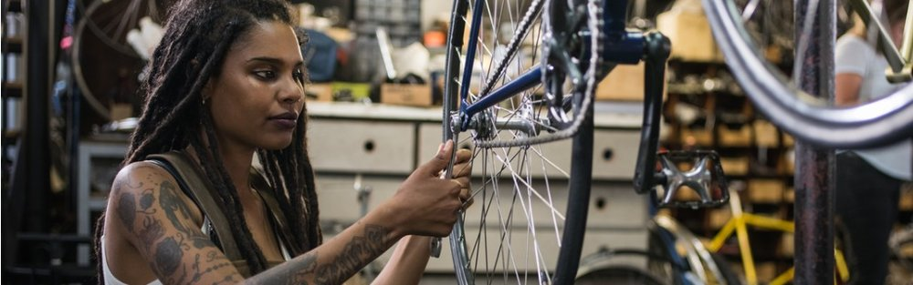 woman-bicycle-mechanic-fixing-a-wheel-in-a-repair-workshop-picture-id514390080.jpg