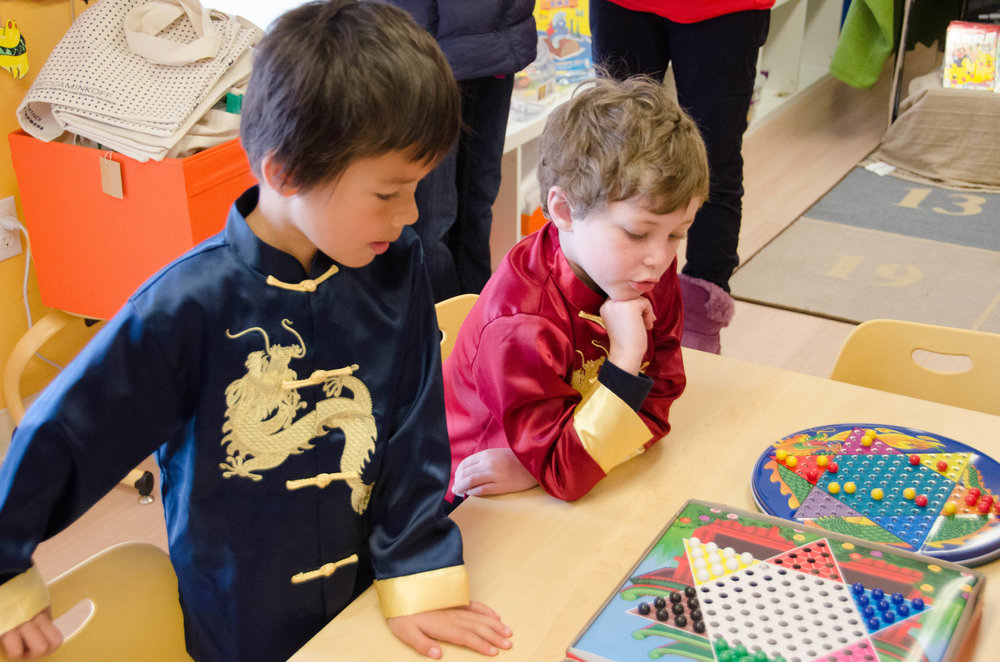 Two kindergarteners playing Chinese checkers in an activity room.