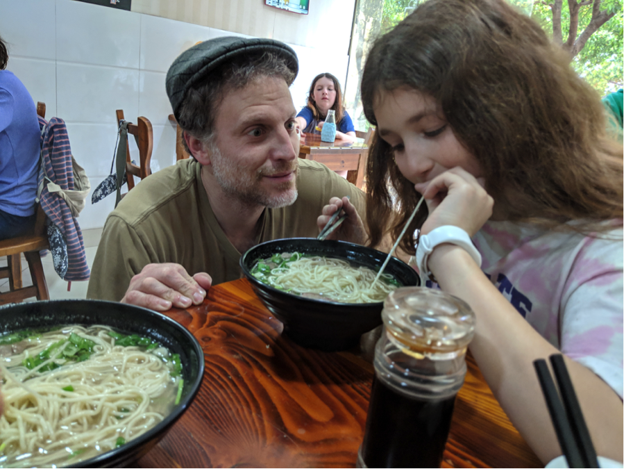 Mike watches a student enjoy her noodles. His obsession with Lanzhou Lamian is legendary.